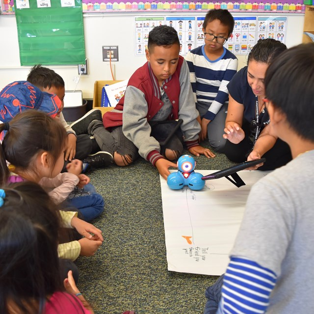 4th grade students help teach TK students to code robots.